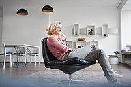 Woman relaxing on leather chair at home - RBF002486