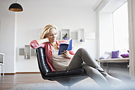 Woman relaxing with book on leather chair at home - RBF002489