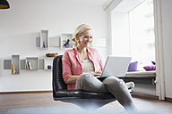 Woman sitting with laptop on leather chair at home - RBF002492
