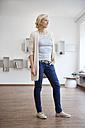 Woman standing in modern living room - RBF002519