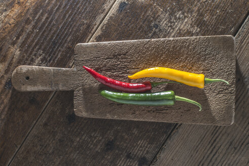 Three chili peppers on old wooden board - DEGF000353