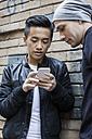 China, Hong Kong, gay couple at house wall looking on cell phone - JUBF000008