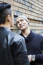 China, Hong Kong, gay couple at house wall - JUBF000004