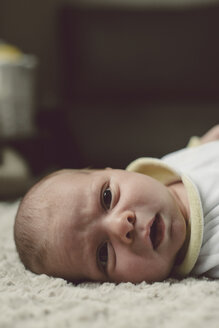 Portrait of baby boy lying on blanket - RAEF000057