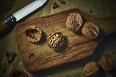 Cracked and whole walnuts on wooden board - DIKF000135