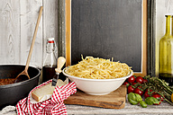 Spaghetti Bolognese, Spaghetti in bowl and sauce Bolognese in pan, board in background - CSTF000889