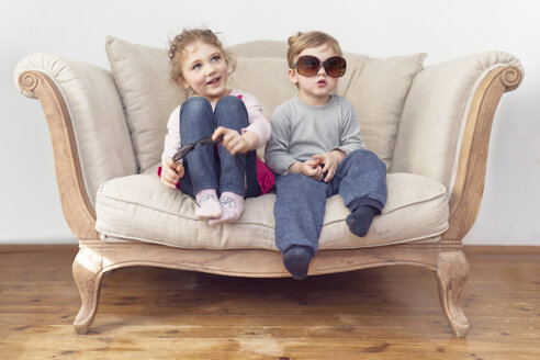 Brother and sister with oversized sunglasses sitting on couch - OPF000039