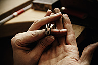 Goldsmith working on wedding rings, hand holding unfinished ring - KRPF001304