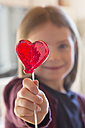 Girl holding heart-shaped lollipop - SARF001477