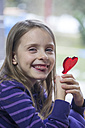 Girl holding heart-shaped lollipop - SARF001431