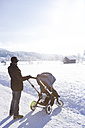 Austria, Salzburg State, Steinernes Meer, mother with baby carriage in winter - DISF001404