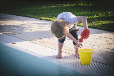 Little girl playing at pool edge with bucket and watering can - GSF001002