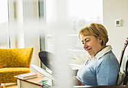 Senior woman at home looking at record - UUF003467