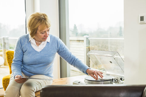 Senior woman at home putting record on record player - UUF003470