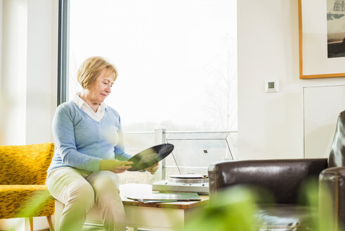 Senior woman at home putting record on record player - UUF003471