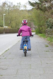 Germany, Kiel, Little girl riding bicycle, rear view - JFEF000601