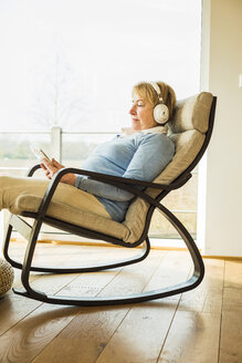 Senior woman at home with headphones and digital tablet - UUF003477
