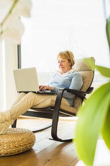 Senior woman at home using laptop - UUF003479