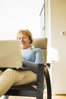 Senior woman at home using laptop - UUF003481