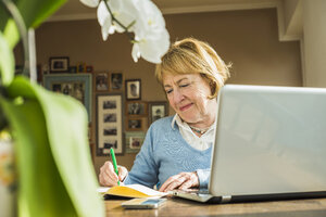Senior woman at home with laptop and notebook - UUF003486