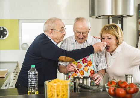 Senior friends cooking in kitchen - UUF003505
