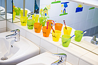Plastic cups with toothbrushes with manes of kids in nursery - JFEF000564