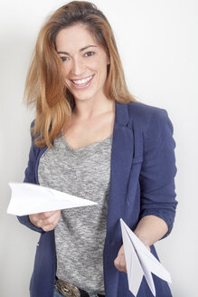 Portrait of smiling woman with paper planes - PATF000027