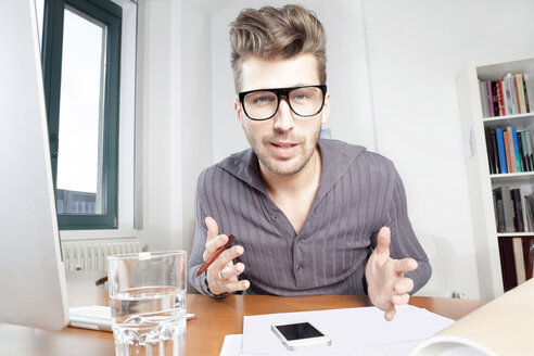Fashionable young man at his desk in an office - PATF000047