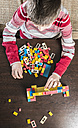 Boy playing with building bricks on a table - DEGF000369