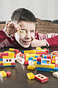 Boy playing with building bricks on a table - DEGF000373