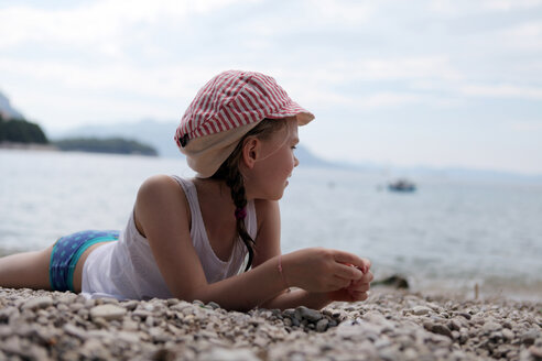 Girl with cap lying on stony beach - SAF000016
