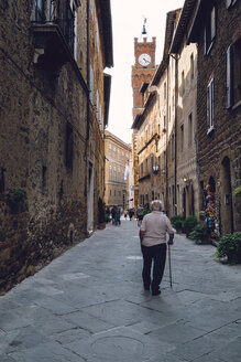 Italy, Tuscany, Pienza, Old man walking in historic old town - GS000955