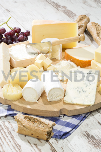 Cheese platter with different sorts of cheese, baguette and grapes on wood - MAEF009870