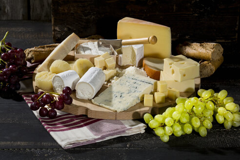 Cheese platter with different sorts of cheese, baguette and grapes on wood - MAEF009872