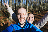 Portrait of happy couple taking a selfie in a forest - GEMF000072