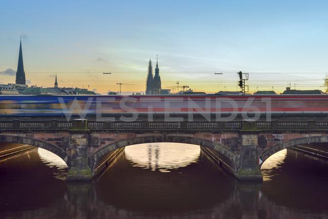Germany, Hamburg, train on Lombard bridge on the Inner Alster Lake at sunset - RJF000405