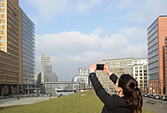 Germany, Berlin, businesswoman taking smartphone picture - BFRF000949
