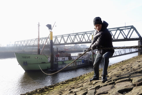 Germany, Bremerhaven, man pulling rope of freight ship - NDF000516