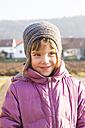 Portrait of little girl wearing woolly hat and pink winter jacket - LVF002944