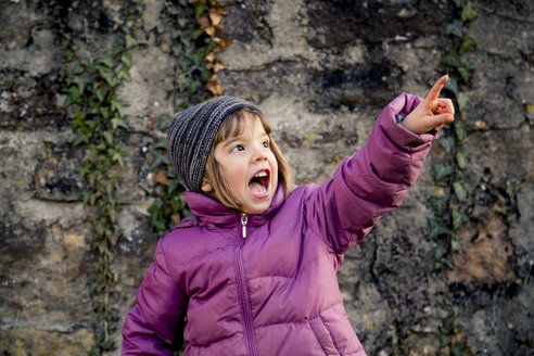 Excited girl wearing woolly hat and pink winter jacket pointing at something - LVF002945