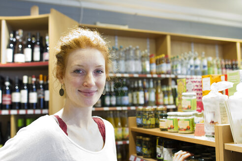 Portrait of smiling young woman in wholefood shop - SGF001389