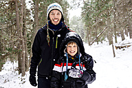 Happy man and boy in the forest while snowing - GEMF000082