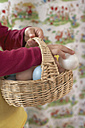 Girl's hands holding wickerbasket with Easter eggs - FSF000332