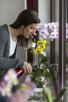 Woman with spray bottle caring about orchid - SHKF000268