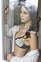 Sensual young woman in lingerie behind windowpane - SHKF000286