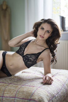 Sensual young woman in lingerie lying on couch - SHKF000298