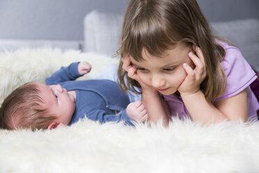 Little girl and newborn brother together on sheepskin - ROMF000055