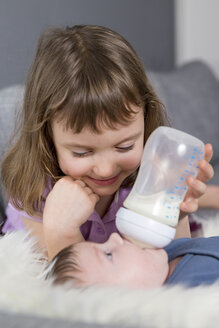 Little girl feeding newborn brother with baby bottle - ROMF000060
