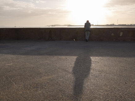 Morocco, Essaouira, man at wall at the coast - STDF000170