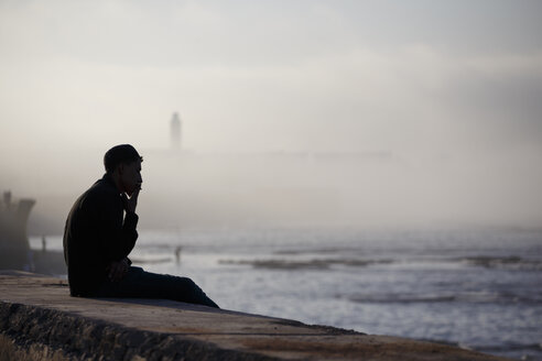 Morocco, Casablanca, man sitting on wall at the coast smoking - STD000122